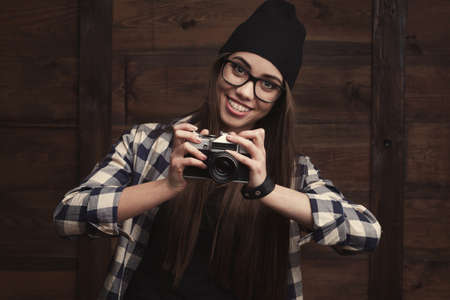 Hipster girl in glasses and black beanie with vintage camera on the wooden