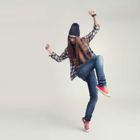 Dancing hipster girl in glasses and black beanie on the grey studio background