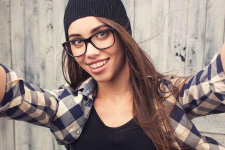 chicas adolescentes: sonriente niña inconformista en copas y tirantes hacer una selfshoot sobre fondo de madera