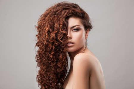 cabello rizado: tiro del estudio de la mujer con el pelo rizado marrón saludable aislado sobre fondo gris