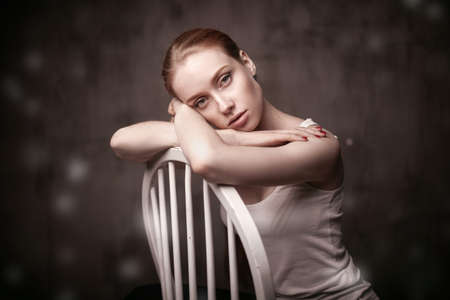 closeup portrait of beautiful woman sitting on a white chair on dakr grey background photo