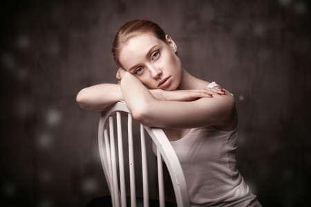 Dakr 회색 배경에 흰색의 자에 앉아 아름 다운 여자의 근접 촬영 초상화 스톡 콘텐츠 - 46703983