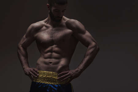 fitness hombres: hombre fuerte de atlética en el fondo degradado gris oscuro