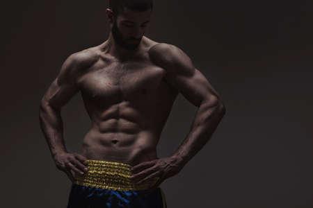 male model torso: strong athletic man on dark grey gradient background