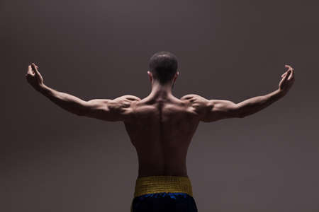 fit: strong athletic mans back on dark grey gradient background