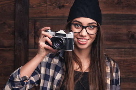 Hipster girl in glasses and braces with vintage camera on the wooden background