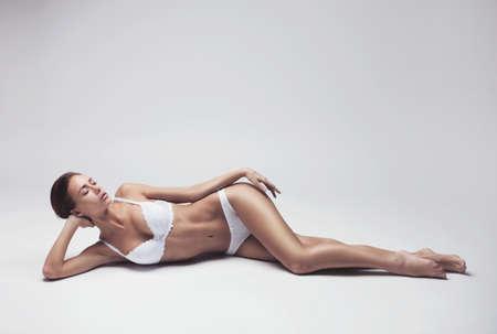 modelo desnuda: hermosa joven en ropa interior blanca que miente sobre un fondo claro Foto de archivo
