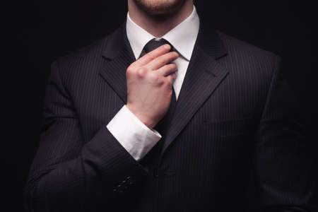 boss: Portrait of young businessmans suit isolated on dark background