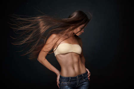 glamour nude: beautiful young athletic brunette woman with long straight flying hair isolated on dark background