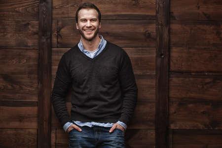 Portrait d'une jeune mannequin de mode homme souriant beau dans le fond en bois urbain Banque d'images