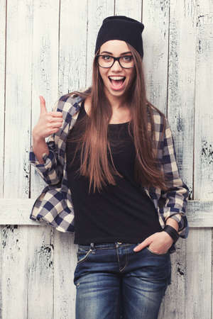 Hipster girl in glasses and black beanie with thumbs up on the wooden background Stockfoto
