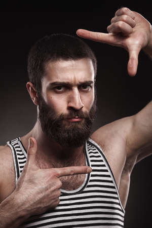 disillusionment: studio portrait of beardy man in singlet on grey gradient background