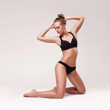 donna che balla: il corpo ritratto di giovane donna ginnastica snella in lingerie nera isolato sulla luce sfondo grigio studio