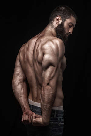 fit man: strong athletic beardy mans back isolated over black background