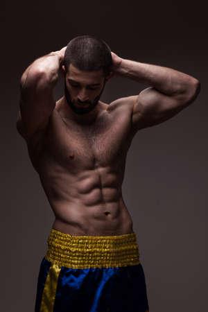 modelos hombres: hombre fuerte de atlética en el fondo degradado gris oscuro