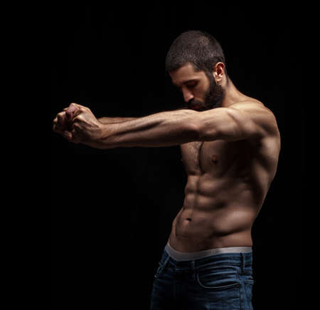 strong athletic beardy man isolated over black background