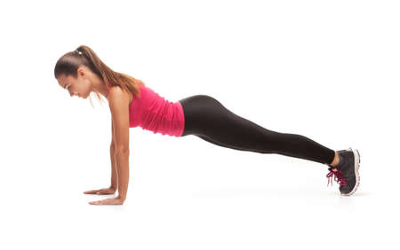 black pants: Fitness woman in pink shirt and black pants doing stretching exercise - isolated over white