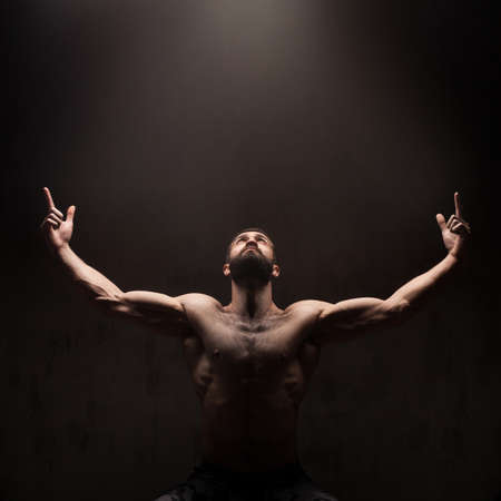 black hands: Man praying on dark studio background. Dramatic light from above