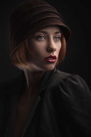 Beautiful blond woman with red lips in retro hat. fashion studio shoot.