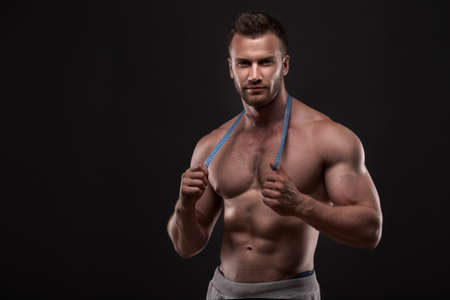 man measurement: Muscular man with measurement tape, isolated on dark grey background