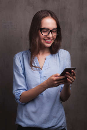 chats: Closeup portrait of beautiful happy young woman with glasses chats by cellphone near grey background grunge wall