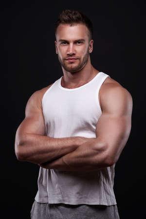 Studio portrait of athletic young man wearing white undershirt isolated on black background