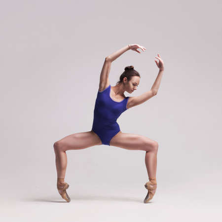 beautiful woman ballet dancer in blue swimsuit posing on isolated light grey studio background Banque d'images
