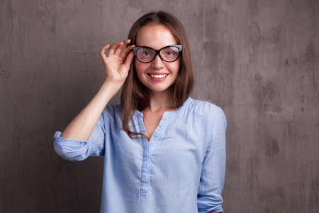 portrait of beautiful happy young woman with glasses near grey background wall