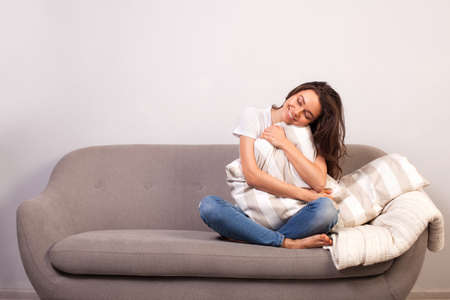 Brunette woman hugging a pillow on the sofa