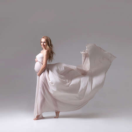 elegant pregnant woman in a white flying dress 스톡 콘텐츠 - 120631577