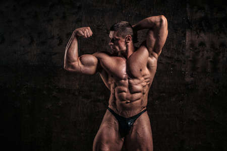 Sporty and healthy muscular man on dark grunge background 스톡 콘텐츠 - 157620462