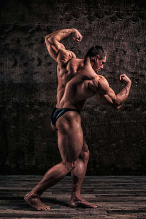 Sporty and healthy muscular man on dark grunge background 스톡 콘텐츠 - 157620464