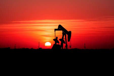 yacimiento petrolero: Puesta de sol y campo petrolero gato de bomba