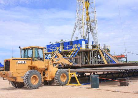 loader: Front End Loader Loading Pipe On Oil Rig