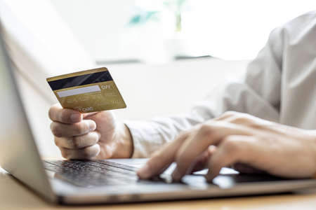 Man holding a credit card and filling out his credit card information on his laptop. Credit cards can be paid for goods and services through general merchants or online stores. Credit card concept.