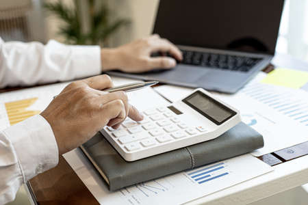 Businessmen press the white calculator to calculate the numbers in the company financial documents, the finance department prepares the document and forwards it to be checked before the meeting.