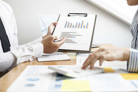 Business women are pressing a to check together with male business partners, they are documenting company finances and verifying the accuracy of the information. Financial concept.