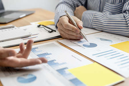 Two businessmen are meeting together on company finances, on a table where there is a paperwork for meetings, meetings and plans together for the company to thrive. The concept of corporate finance.