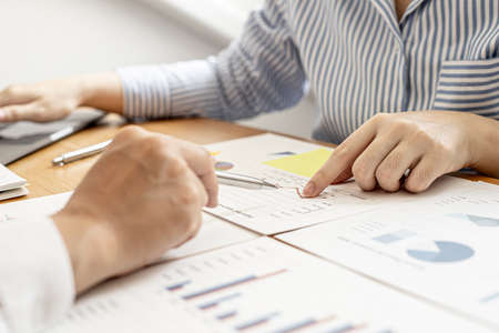 Two businessmen are examining the information in the company's financial documents provided by the finance department, they brainstorm to develop the company to further growth. Financial concept.