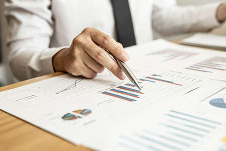 A close-up of a financial businessman holding a pen and pointing at the information sheet on his desk, reading the company's financials to make a financial plan. Financial concept.
