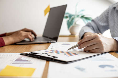 Two salespeople are working together to prepare a company sales report to bring to the monthly general meeting with the management. Sales management concept.