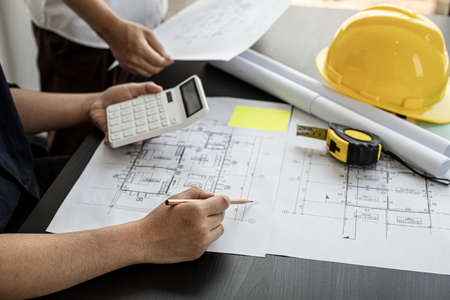 The architect was pressing the white calculator and there was an engineer standing there holding the floor plan. They are examining the draft blueprint for the designed building.