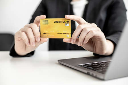 A business woman holds a credit card to make payments on the website where she is shopping online. Concept of using credit cards to pay for goods and services on online websites.