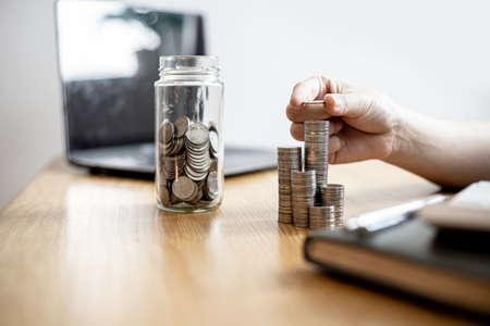 A woman is stacking coins in a row and a jar with a lot of coins, she is doing an income statement and dividing the money for saving. Concept of saving money and investing it to grow money. Archivio Fotografico