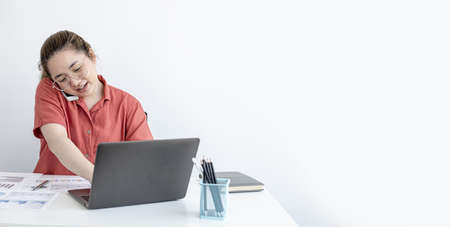 A businesswoman talking on the phone with a personal secretary, she is working from home according to company policy, she uses a laptop to chat and confer with a partner. copy space.