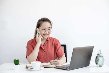 A businesswoman talking on the phone with a personal secretary, she is working from home according to company policy, she uses a laptop to chat and confer with a partner. The idea of working from home