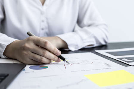 A close-up businesswoman holding a pen and pointing at a company financial statement, she is checking monthly financial documents from the finance department. The financial concept of the company.