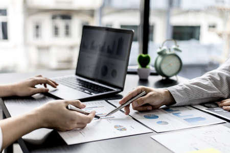 Two business partners are brainstorming on planning, managing and solving company problems, they are pointing at the company financial documents. The concept of business management for growth. Banque d'images