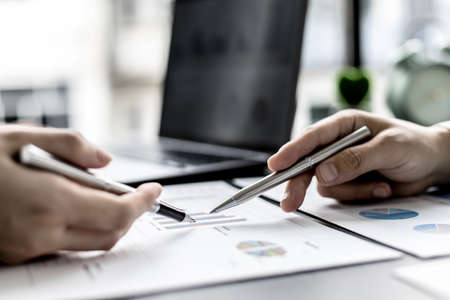 Two business partners are brainstorming on planning, managing and solving company problems, they are pointing at the company financial documents. The concept of business management for growth.