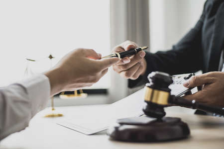 Attorney gives the client a pen to sign a contract admitting fraud, lawyer admits a fraud case in which client is a victim and will sue defendant who is a commercial partner. Fraud litigation concept.